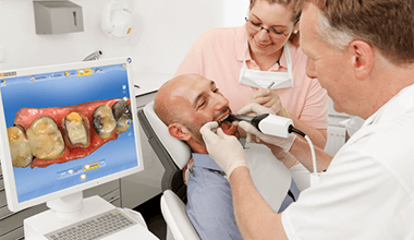 dentist taking digital scan of smiling man's teeth