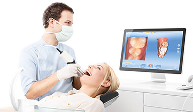 dentist taking CEREC digital bite impressions of smiling woman's teeth