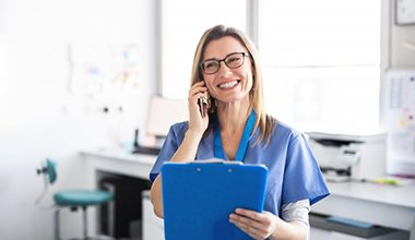 dental team member making phone call and holding blue clipboard