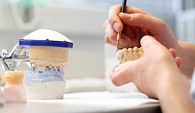 Technician fitting crown and bridge on dental mock-up