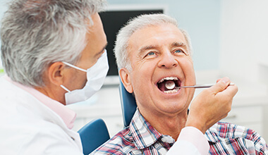Smiling man receiving dental exam from dentist