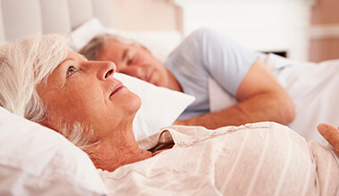 Worthington Sleep Apnea Therapy woman laying awake in bed next to sleeping man