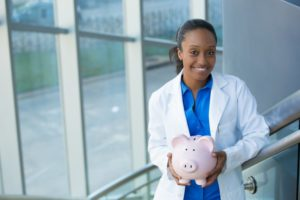 smiling dentist in Worthington holding pink piggy bank
